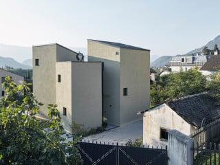 Vier Türme mit unterschiedlichen Geschosshöhen bilden den unkonventionellen Wohnbau Haus D in Kaltern an der Weinstraße