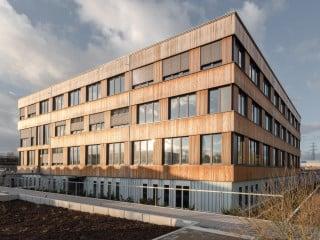 Unweit des ehemaligen Firmensitzes ist nun der erste von mehreren Bauabschnitten fertig gestellt, ein erweiterbarer Holz-Beton-Hybrid nach Plänen von ZRS Architekten Ingenieure