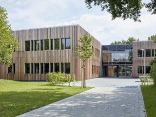 Umgeben von dichtem Baumbestand und weitläufigen Feldern befindet sich zwischen mehrgeschossigen Wohnbauten die fünfzügige Grundschule Rahewinkel nach dem Entwurf des Planungsbüros Rohling Architekten Ingenieure