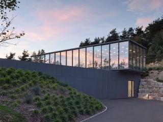 Das als Quader aufgesetzte, transparente Obgerschoss des Wohnhauses kontrastiert mit dem geschlossen wirkenden Erdgeschoss (Südostansicht)