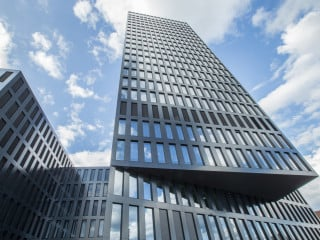 Der 78 Meter in die Höhe ragende Grosspeter Tower mit dunkler Rasterfassade setzt einen städtebaulichen Akzent in Basel; der Entwurf stammt vom Architekturbüro Burckhardt+Partner