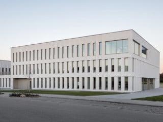 Der vom Architekturbüro Landau + Kindelbacher entworfene Firmensitz eines Kosmetikkonzerns steht am Rand des örtlichen Gewerbegebiets von Sauerlach und grenzt im Osten an Wiesen und Felder.