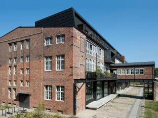 Südansicht des ehemaligen Werkstattgebäudes mit markanter Erschließungsbrücke und aufgestocktem Dachgeschoss