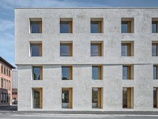 Der neue Bürobau Emmenweid mit graumelierter Kalkputzfassade von Baumschlager Eberle Architekten steht an der Stelle des historischen Crinolbaus, einem Industriegebäude aus dem 19. Jahrhundert.