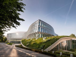 Der IOC-Hauptsitz von 3XN und Itten Brechbühl in Lausanne fällt durch seine geschwungene Doppelfassade aus Glas auf.