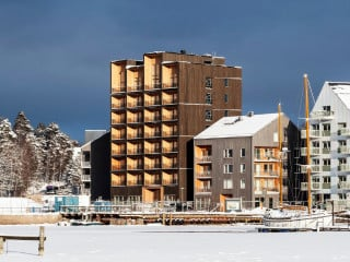 Am Ufer des Sees Mälaren haben C.F. Møller Architects einen neungeschossigen Wohnturm aus vorgefertigten Brettsperrholzelementen errichtet.