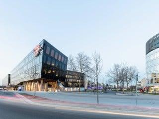 Im Westen des Entwicklungsgebiets Grüne Mitte Essen bildet die neue Verlagszentrale der Funke Mediengruppe den städtebaulichen Schlussstein. Entworfen wurde das Ensemble vom Wiener Architekturbüro AllesWirdGut.