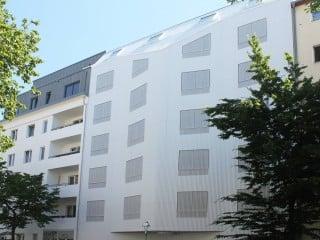 Der Geschosswohnungsbau von Rundzwei Architekten in Berlin-Moabit zeigt sich zur Straße hin mit einer Außenhaut aus gewelltem Aluminium.