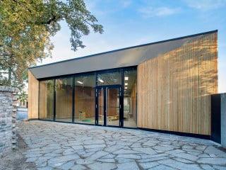 Das Familienzentrum Hippolytusgarten umfasst im Wesentlichen eine Kindertagesstätte: Das langgestreckte, abgewinkelte Gebäude öffnet sich an beiden Enden.