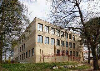 Der qudaderförmige Neubau der neuen Carl-Platz-Schule in Herzogenaurach ergänzt ein Ensemble aus Bestandsgebäude. Im Erweiterungsbau finden zusätzliche Klassenzimmer, eine Lernwerkstatt sowie die Mittagsbetreuung Platz.