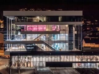 Die von Burckhardt+Partner entworfene Schindler City Center bei Nacht. Im Sockel befinden sich die Cafeteria und das Personalrestaurant, in den auskragenden Obergeschossen die Ausstellung und der Gästebereich.