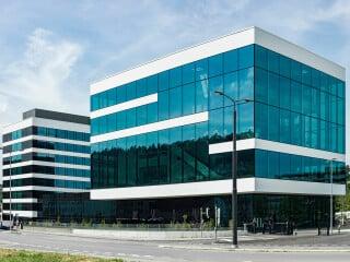 Das neue Ausstellungsgebäude (vorne im Bild) ist über einen dunkel verglasten Sockel mit dem umgebauten Verwaltungssitz verbunden.