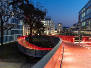 Netzwerkarchitekten und Tragraum Ingenieure haben in Darmstadt eine Fuß- und Radwegbrücke konzipiert, die sich wie eine Schlange über die vielbefahrene Rheinstraße windet.