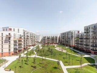 Rund um einen großen grünen Innenhof mit Bäumen, Wiesen und Spielflächen formiert sich am Wiener Kapellenweg ein neues Wohnquartier.