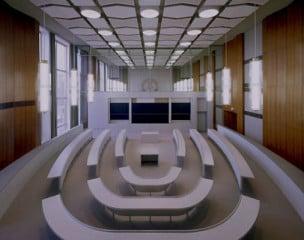 Der zweigeteilte Sitzungssaal: das ehemalige Staatswappen der DDR im Hintergrund