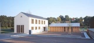 Drei-Seit-Hofanlage mit doppelstöckigem Haupthaus links, eingeschossigem Jugendklub in der Mitte und der Garagenzeilen rechts