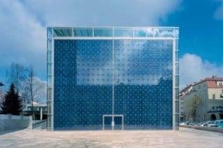 Die geschlossene Front des blauen gläsernen Kubus besteht aus kleinen Quadraten