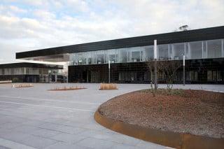 Eingangsgebäude mit auskragendem Dach über der Zufahrt zum Gelände