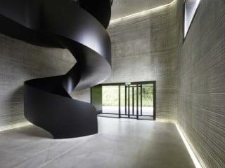 Wände aus gerilltem Sichtbeton und skulpturaler Treppe aus schwarzem Stahlblech im Eingangsbereich. Foto: Hannes Henz, Zürich