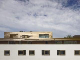 Auf der Gartenseite des Gebäudes sind Balkone in die Fassade eingeschnitten