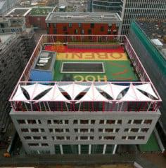 Im Vordergrund das Schulhaus, dahinter das achtgeschossige Wohngebäude