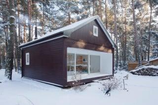 Im Kontrast zur dunkelbraun lasierten Kiefernholzverschalung der Fassade stehen die Fassadenöffnungen mit Blendrahmen in Weiß lackiertem Holz